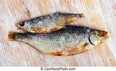 Salt dried roach - Dried salted roach fish on wooden table, ...