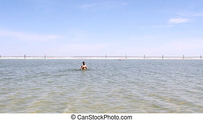 Salt Lake Baskunchak, Russia. May 11, 2013. Man swimming .