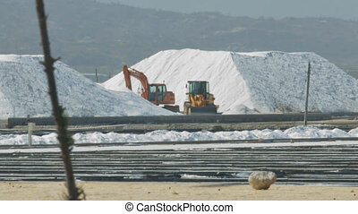 huge salt mining site with white hills high and modern grader and excavator against mountains