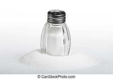 Salt on black background - Salt and saltshaker on white...