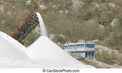 huge white salt pile poured by modern combine machine against rocky hill near strange blue building