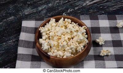 Salt popcorn on dark background. falling into a bowl slow motion