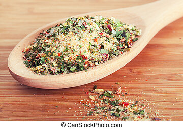 Salt with various herbs in a wooden spoon
