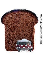 Saltcellar with salt against a slice of black bread.