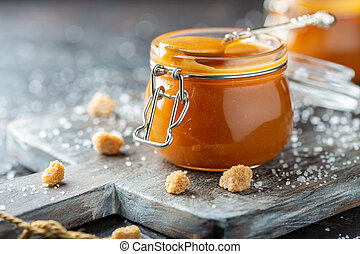 Salted caramel and a spoon in a glass jar.