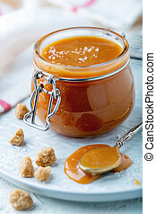 Salted caramel in a jar on a white plate.