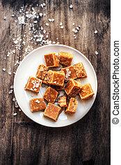 Salted caramel pieces and sea salt close up. Butter caramel candy macro