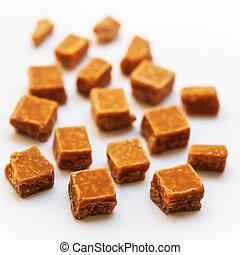 Salted caramel pieces and sea salt close up over white background. Butter caramel candy macro. Vintage rustic style