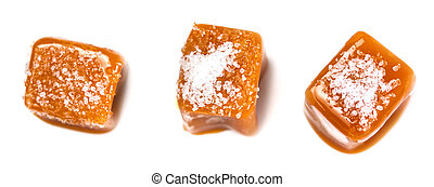 Salted caramel pieces and sea salt isolated on white background. Golden Butterscotch toffee caramels. Toffees, macro.