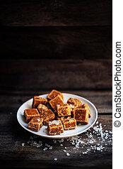 Salted caramel pieces and sea salt macro. Butter caramel candy macro.