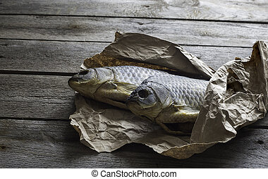 Salted Dry fish vobla on crumpled craft paper on wooden background, delicious beer snack, close-up.