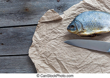 Salted Dry fish vobla with a sharp knife on crumpled craft paper on wooden background, delicious beer snack, close-up.