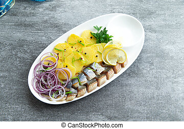 Salted herring and boiled potatoes in a plate.