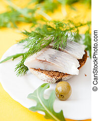 salted herring fillet on a piece of bread
