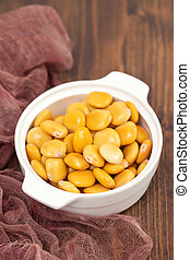 salted lupins in white bowl on brown wooden background