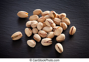Salted pistachios on a black slate background