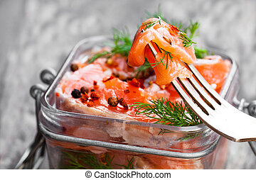 Salted  salmon with herbs in glass jar on wooden background