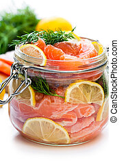 Salted  salmon with lemon in glass jar isolated on white background