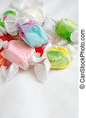 A pile of multicolored saltwater taffy candy on a white cloth.