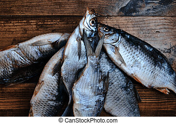 Salty dry river fish on a dark wooden background. Dry fish in the market. Street food.