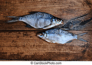 Salty dry river fish on a dark wooden background. Dry fish ...