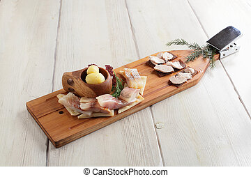 salty fish assorti with potato on wooden plate - salty fish...