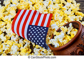Salty popcorn in a wooden cup American flag flying, flag USA...