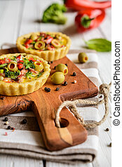 Salty tartlets with bacon, bell pepper, broccoli, cheese, onion, egg and olives