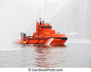Salvage orange tugboat with two big water jets in the Ferrol estuary.