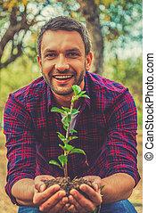salvar, a, environment!, feliz, homem jovem, esticar, saída, planta, em, a, chão, e, olhando câmera, enquanto, ficar, jardim