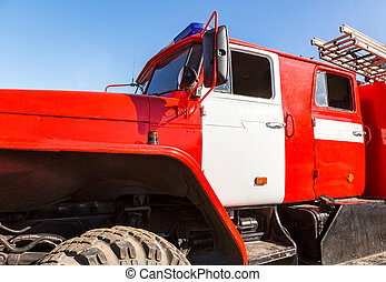 Red fire truck with flashing blue siren light and stair against the blue sky