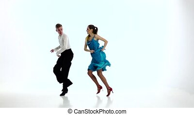 Samba dancing couple of professional elegant dancers,slow motion. White studio