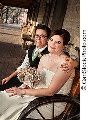 Caucasian lesbian newlyweds sitting on rustic bench
