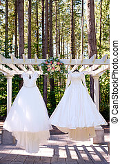 Same Sex Wedding Dresses - Two dresses hanging on a pergola...
