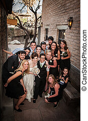 Group from a same sex wedding sitting outside near brick wall