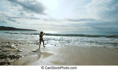 samica, młody, dotykanie, ocean., podróżnik, dziewczyna, jej, urlop, czarnoskóry, cieszący się, godny podziwu, szczęśliwy, balinese, wyścigi, skokowy, wzdłuż, chód, piasek plaża, bikini, seashore., posiadanie