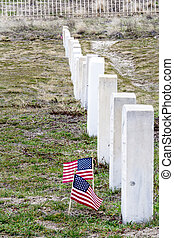 Samll americal flaggs flap in the wind at a military cemetery