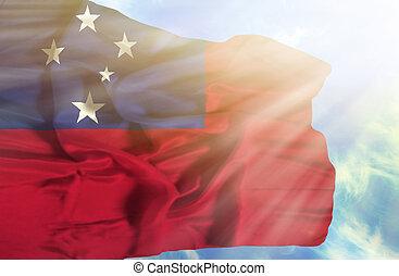 Samoa waving flag against blue sky with sunrays