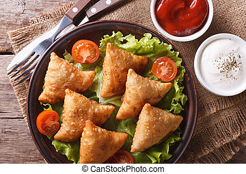 samosa on a plate with sauce and tomatoes closeup. horizontal view from above, rustic style
