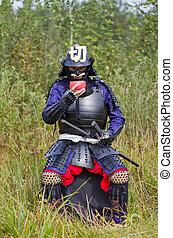 Samurai in armor drinking from bowl