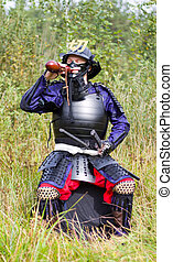 Samurai in armor drinking from flask