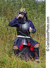Samurai in armor drinking sake from cup