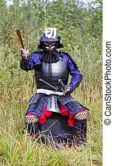 Samurai in armor showing direction by folded fan