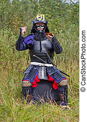 Samurai in armor with chopsticks and plate