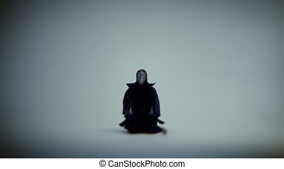 Samurai kendo sits and meditates in a white room. Medium to...