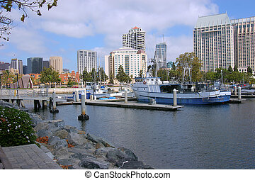Fishing vessels moored at the San Diego marina. Modern buildings and businesses in the surroundings.