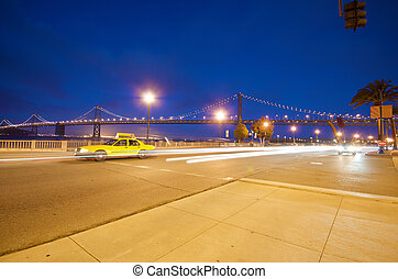 San Francisco Bay Bridge at night with cab
