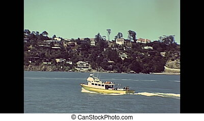 boat tour in San Francisco Bay: city skyline, bridges, Alcatraz Island and Sausalito residential area. Sea view from touristic boat tour. Archival San Francisco in California, United States in 1980.