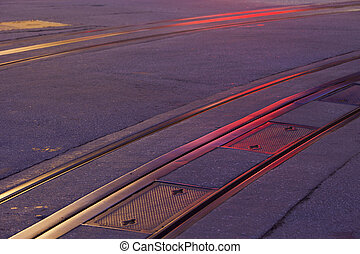 San Francisco historic cable car tracks at night with red and yellow neon light reflections