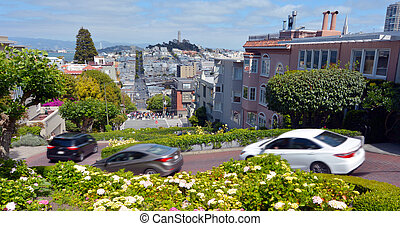 SAN FRANCISCO - MAY 20 2015:Panoramic view of Lombard Street switchback against San Francisco skyline. Lombard Street is known for it's 8 sharp turns make it the most crooked street in the world.